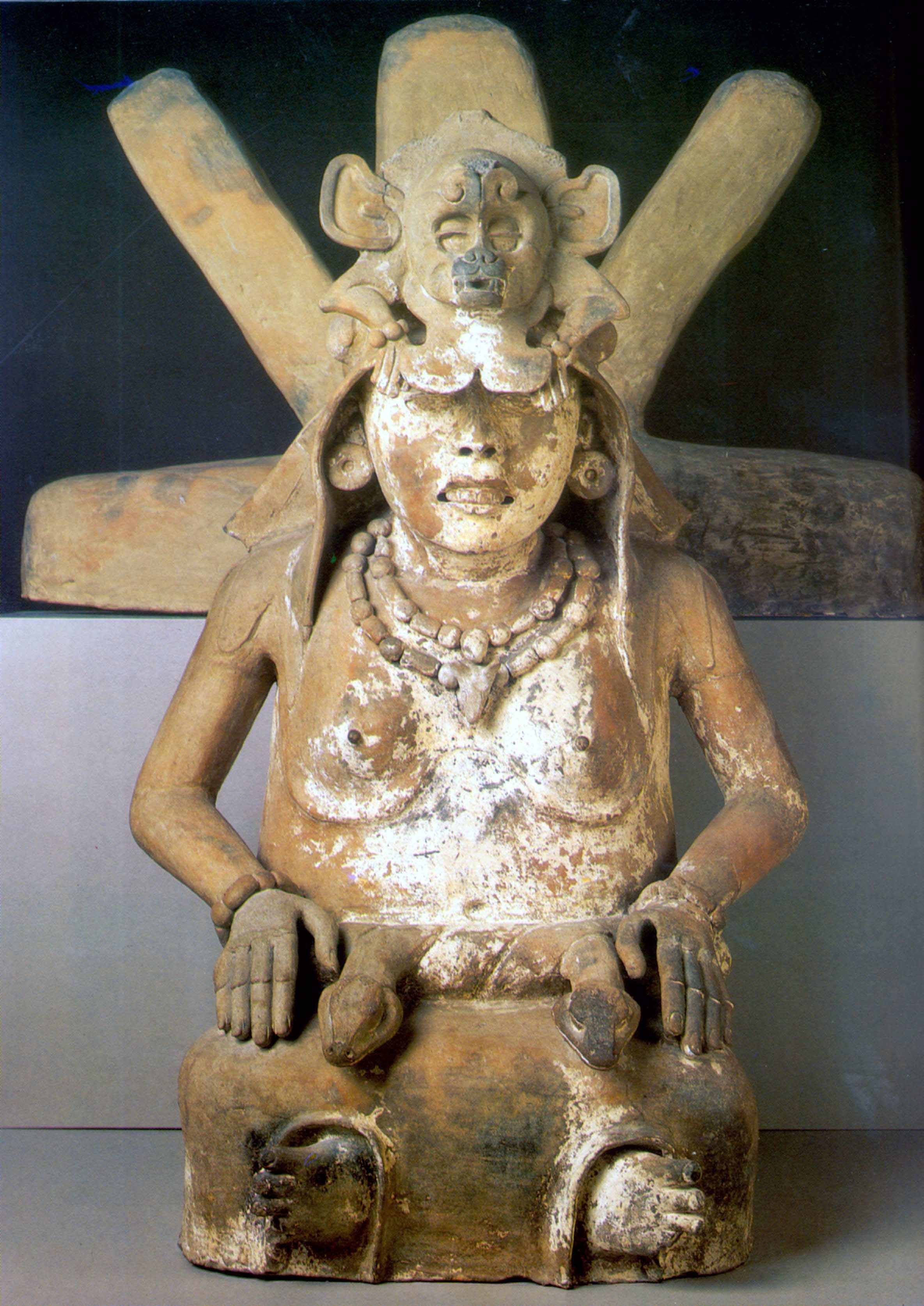 The corpus of monumental ceramic sculpture at El Zapotal includes four seated Cihuateteotl figures. Like their standing companions, they wear long skirts with serpent belts, elaborate headdresses, necklaces, and bracelets. One writer has suggested they represent midwives. This example has a unique five-point device behind her head.