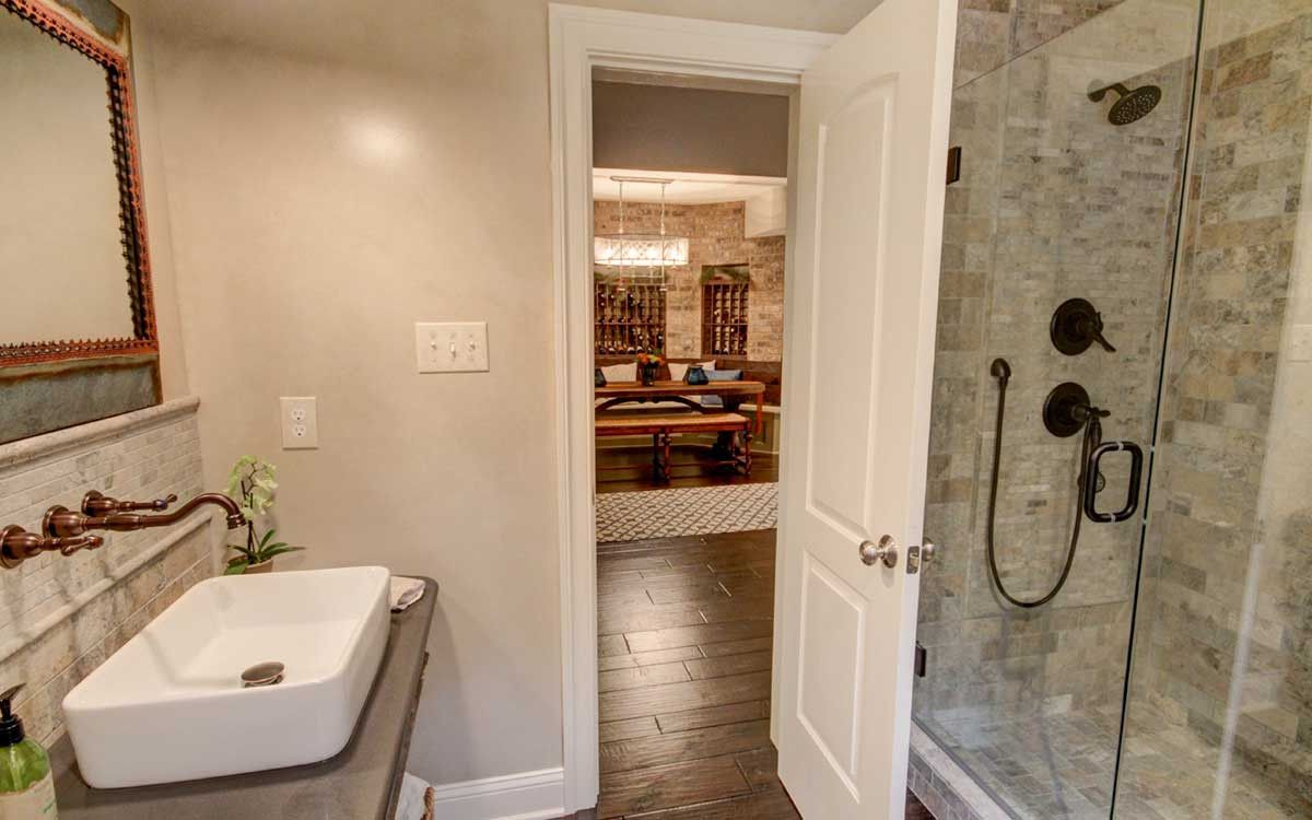 Warm and rustic bathroom features bronze fixtures wood tile floors warm and rustic bathroom features bronze fixtures wood tile floors and rough stone tile work dailygadgetfo Images