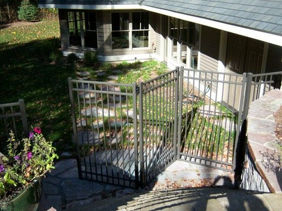 Tri Fold Ornamental Aluminum Gate In Front Of Stair Case