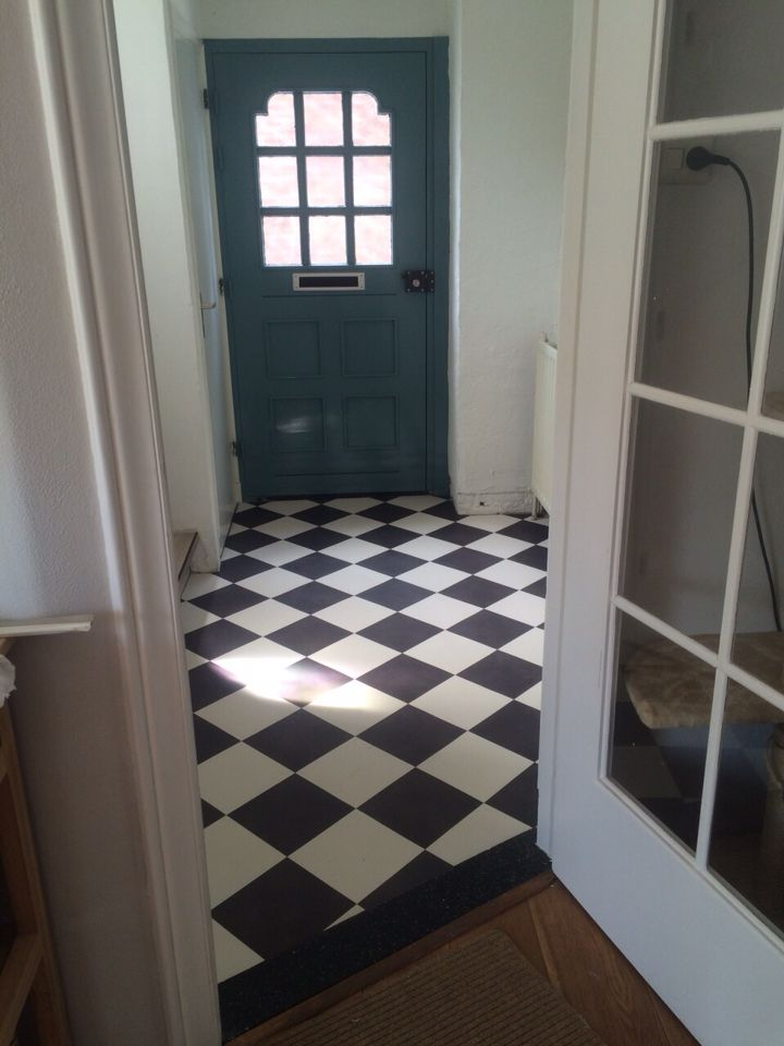 Our hall after a few days work! White and black tiled floor from Flexxfloors. The front door is blue, green or grey depending on the light. Still want to cover the right wall with wood.