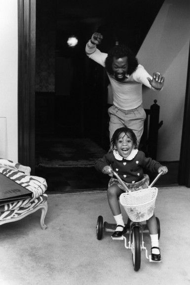 Nick Ashford, of husband and wife songwriting duo Ashford & Simpson, enjoys chasing his daughter Nicole as she rides her tricycle i...