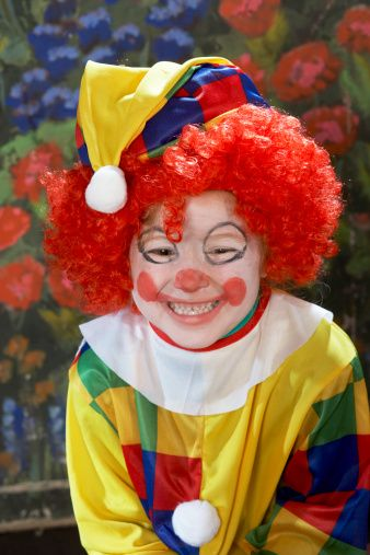 Girl (4-6) wearing clown costume, smiling, close-up