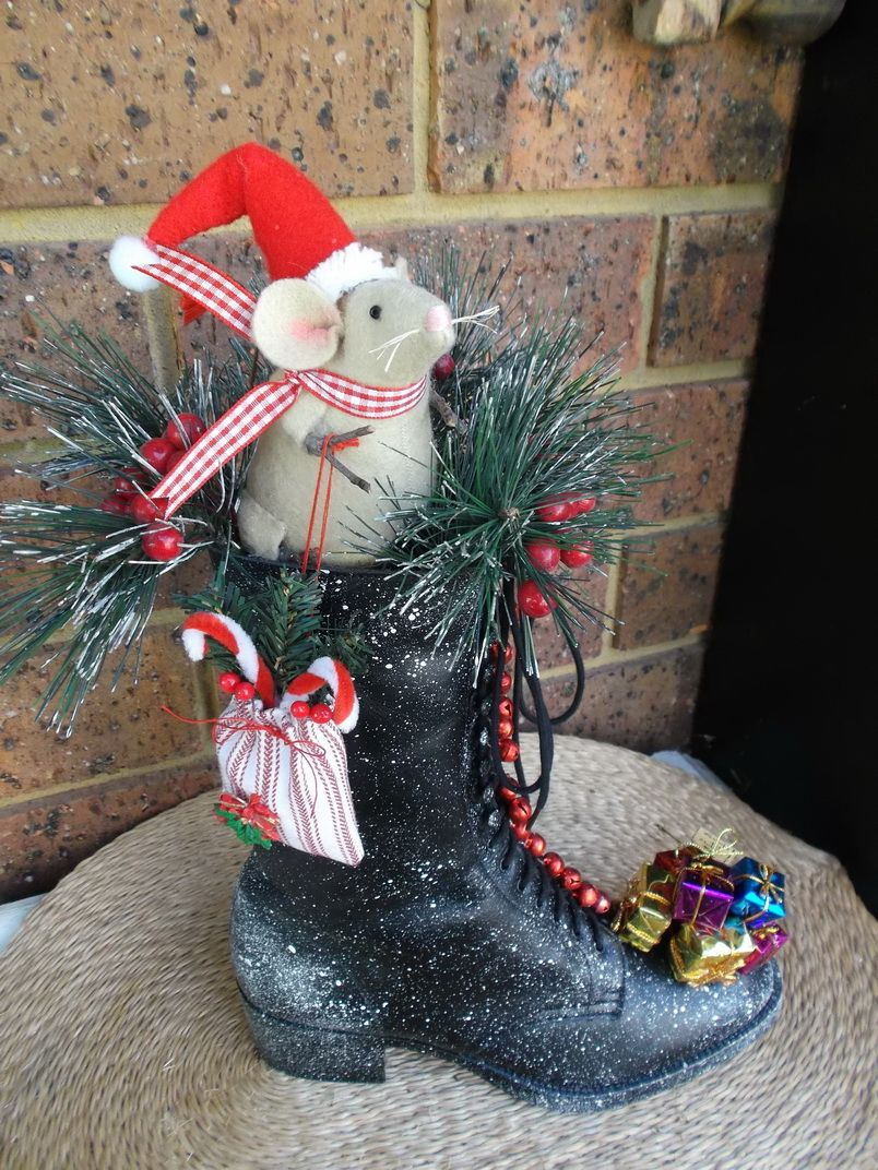 Santa mouse in an old boot, decked out with greenery, berries and bells... Santa left some presents and is holding a little sack.