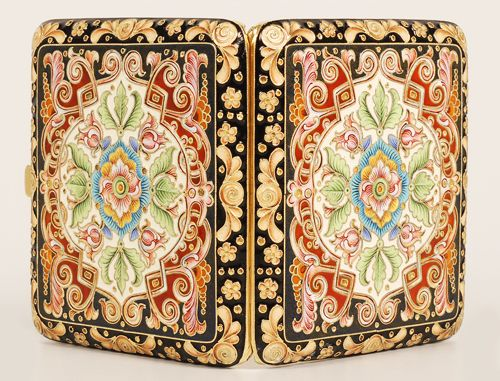 A Russian silver gilt and cloisonné enamel cigarette case, Feodor Ruckert, 1896-1908. Both sides lavishly decorated in multi-color shaded enamel scroll, floral, and geometric motifs within a border of stylized amber colored floral designs against a black enamel ground.