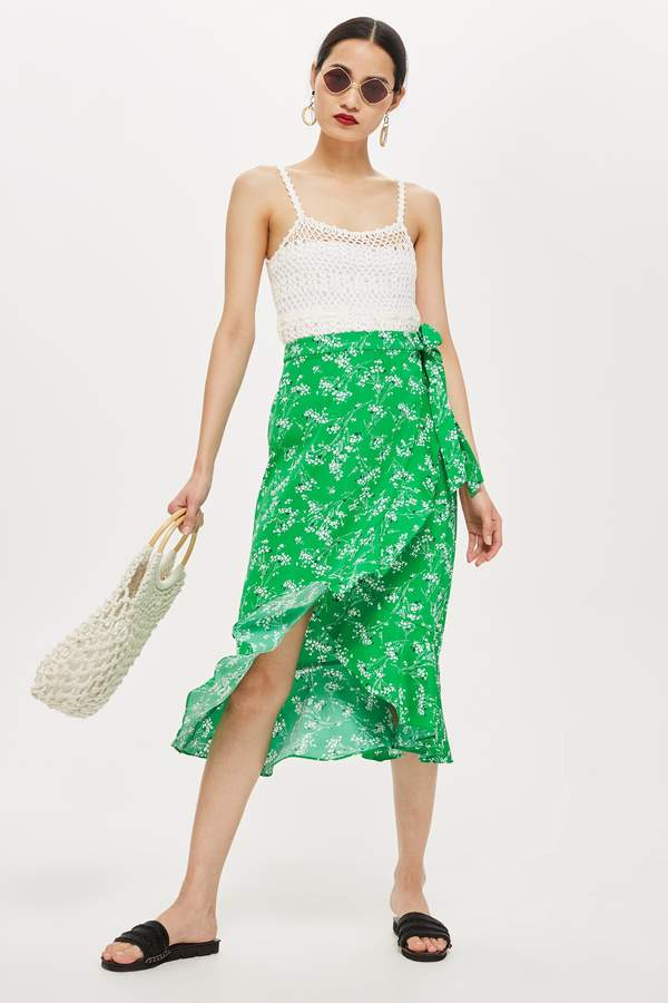 5dfde73a8 Green midi wrap skirt with white floral print and ruffle detail on wrap.  100% Polyester. Machine wash.