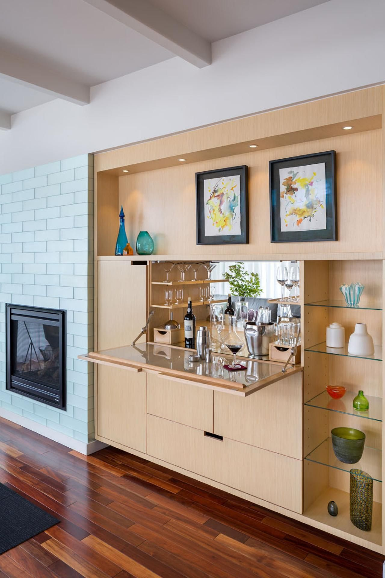 A drop-down door in the sleek, modern built-in cabinetry opens to ...