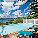Turquoise cushions, on the lounge chairs, echo the vibrant skies above this hillside pool with its incredible views of the ocean beyond.
