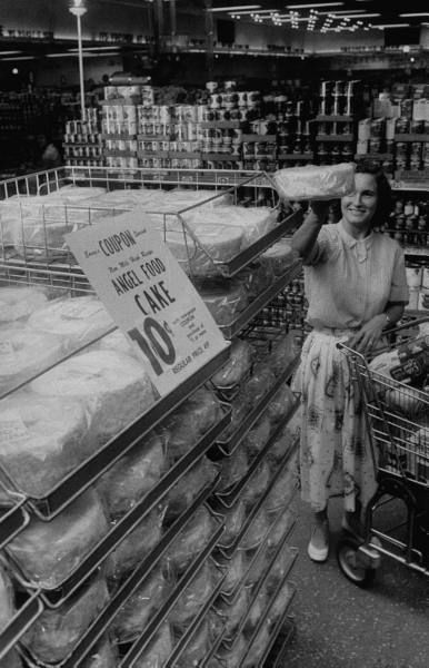 A customer selecting a (ten cent!) angel food cake from the shelves of an Indiana grocery store, 1957. #vintage #supermarket #shopping #1950s #homemaker