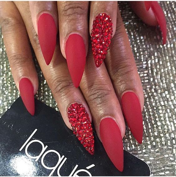 Red Matte Stiletto Nails with Red Rhinestones -  Another way to make red nails even sexier is to opt for a stiletto shape. No matter what nail color - #Matte #Nails #Red #Rhinestones #stiletto