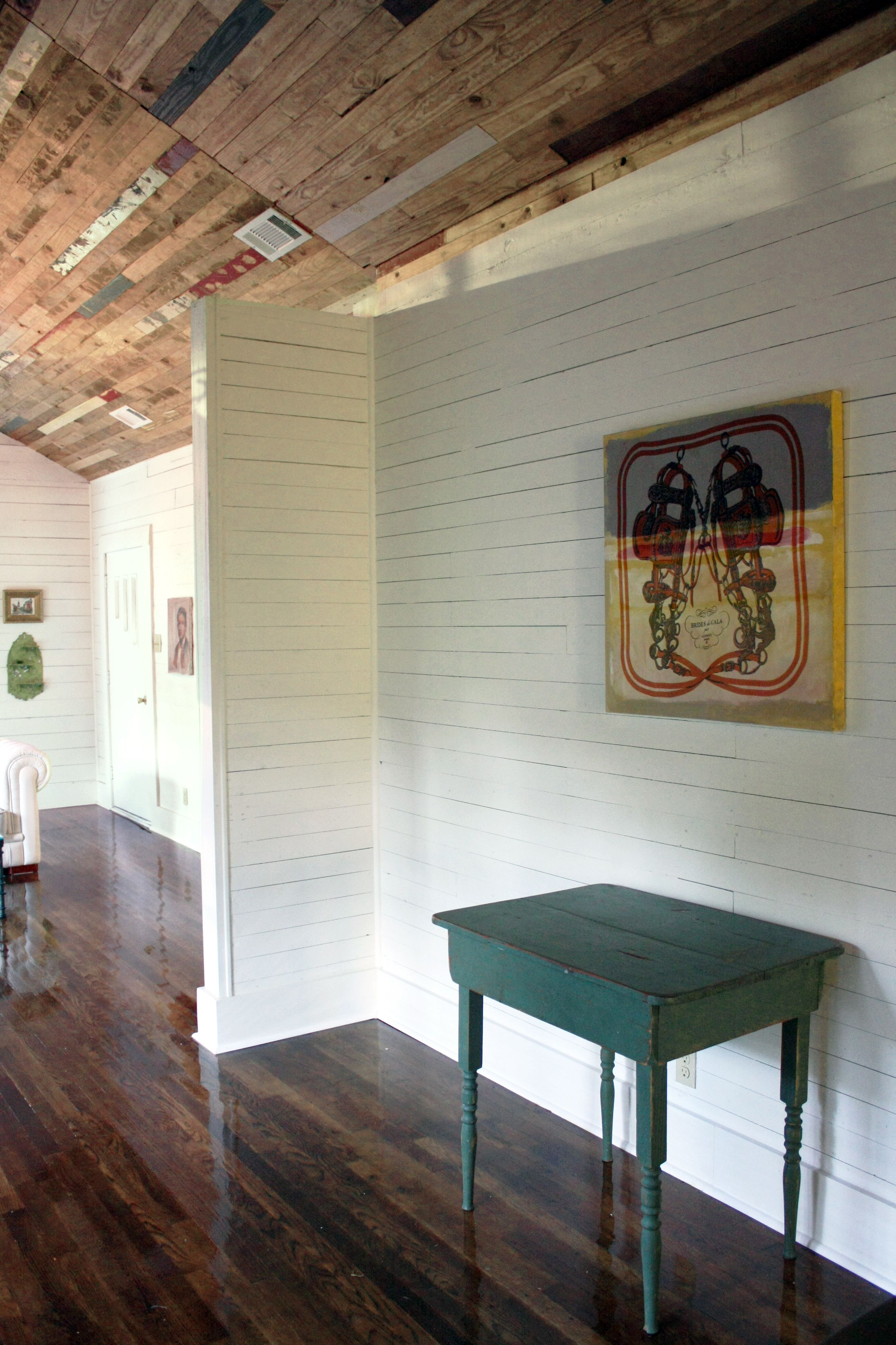 Reclaimed wood ceiling above white ship walls which feature an