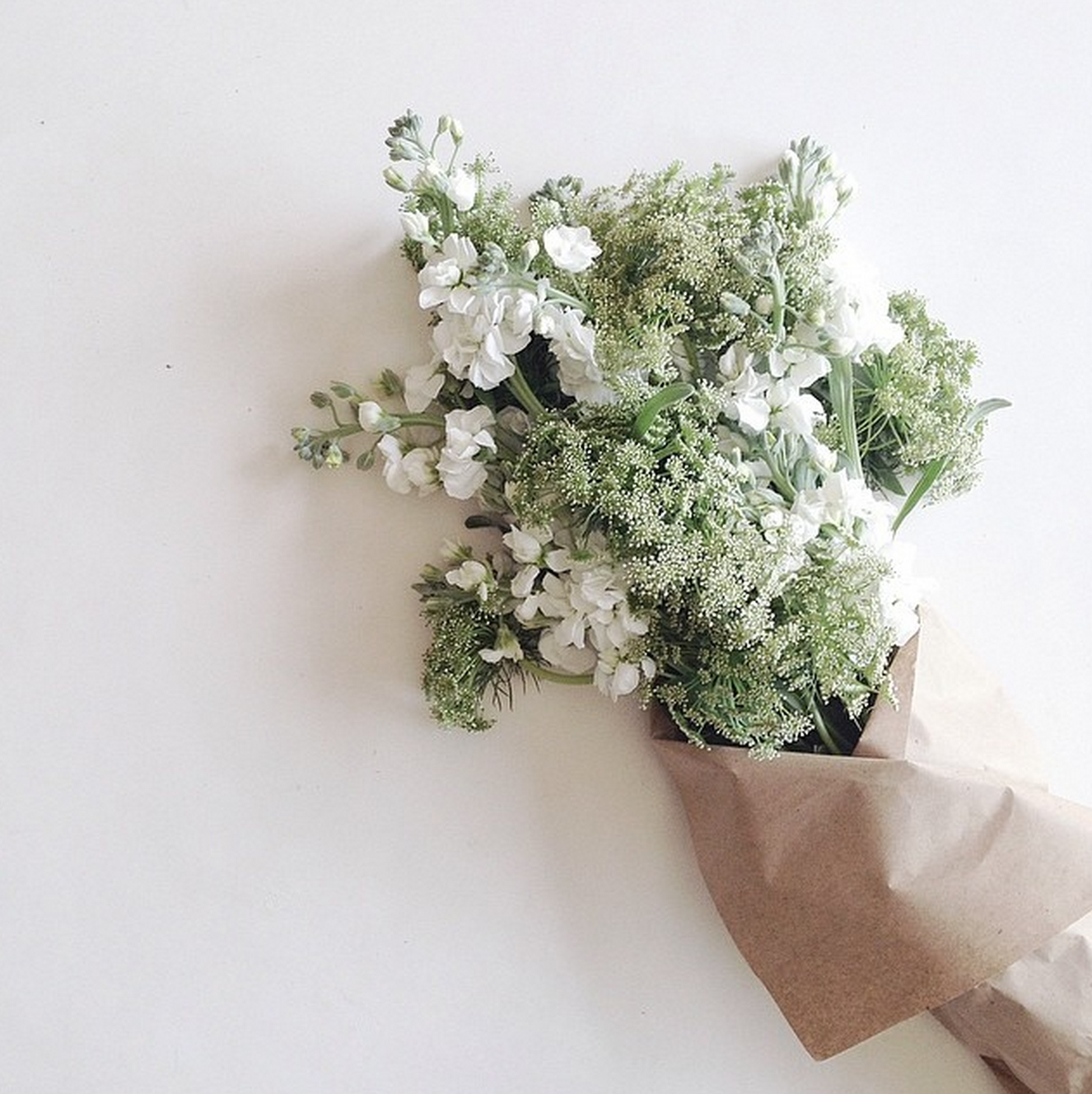 Intricate White Blooms Light Green Bouquet Wrapped In Brown Paper
