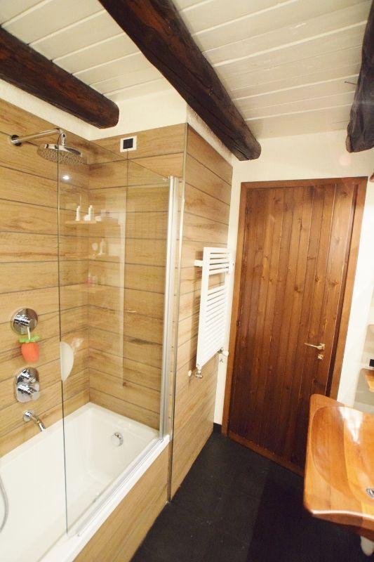 Bagno di montagna con rivestimento doccia/vasca con doghe di gres ...