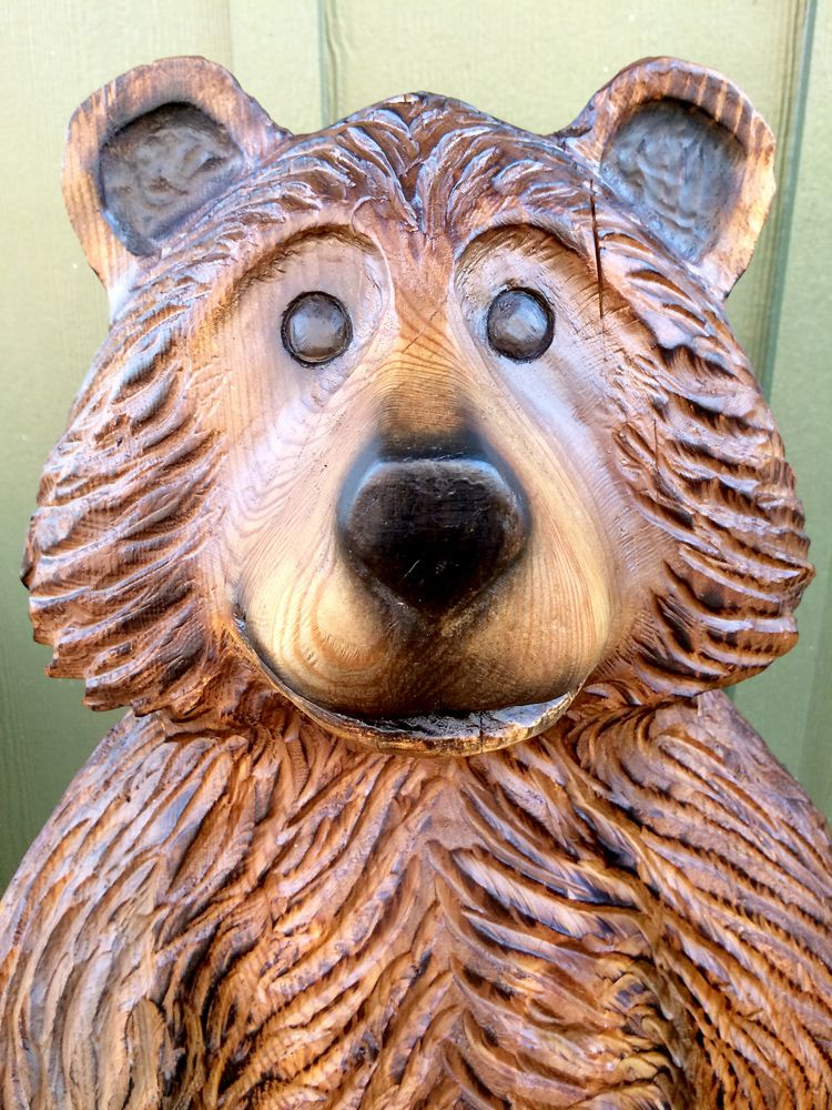 Cartoon style brown bear chainsaw carving in virginia pine