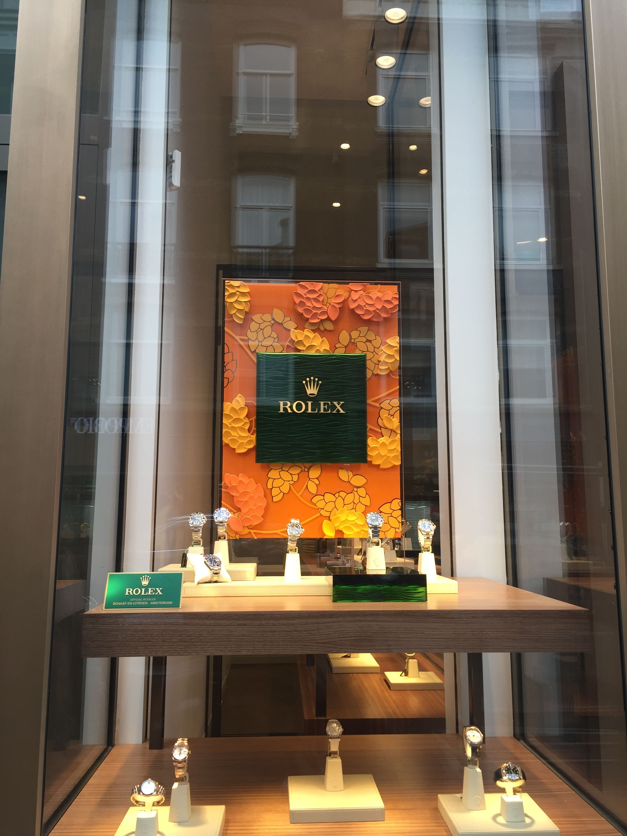 cbf282d544c This was taken in front of a Rolex store. The photo is displaying different  styles of Rolexes. I found the green square Rolex logo against an orange ...