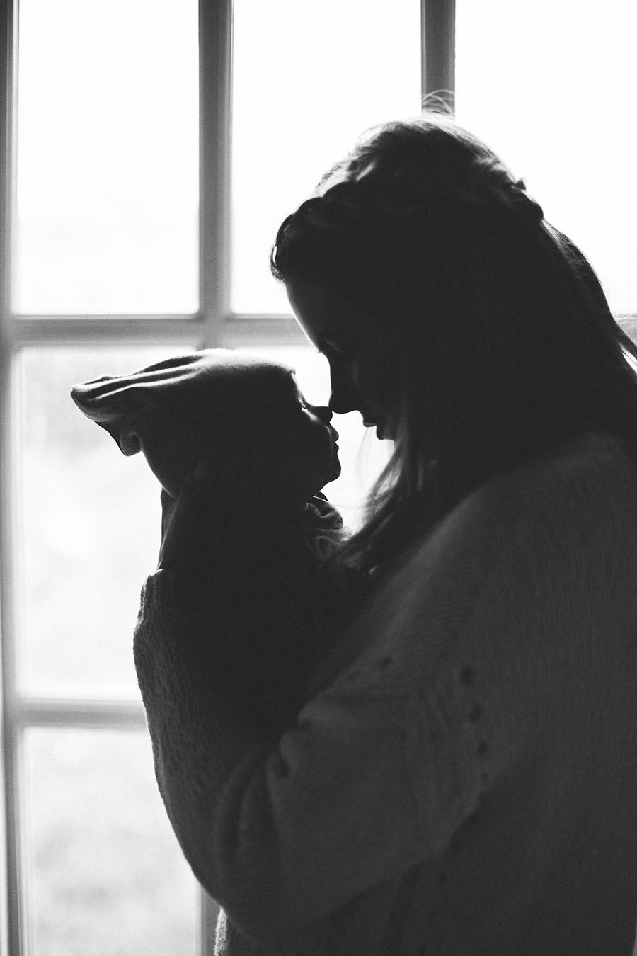 Mother and child baby black and white standing in front if window little cap hat cable knit sweater