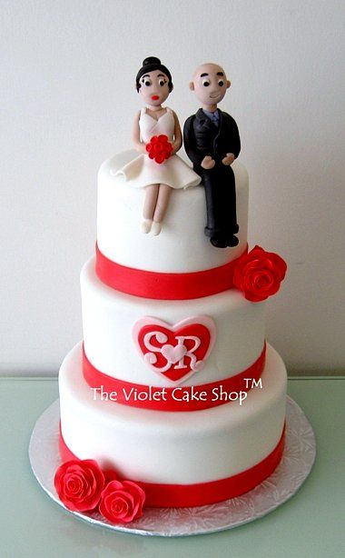 """3 tier traditional red and white wedding cake. Bottom is 9"""", middle is 7"""" and top is 5"""". Iced in buttercream and covered in fondant with fondant ribbon border and roses. 3D bride and groom toppers and monogram decal are handmade from fondant"""