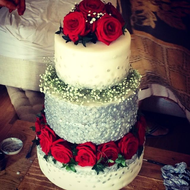 Beautiful wedding cake with red roses and silver sequins.