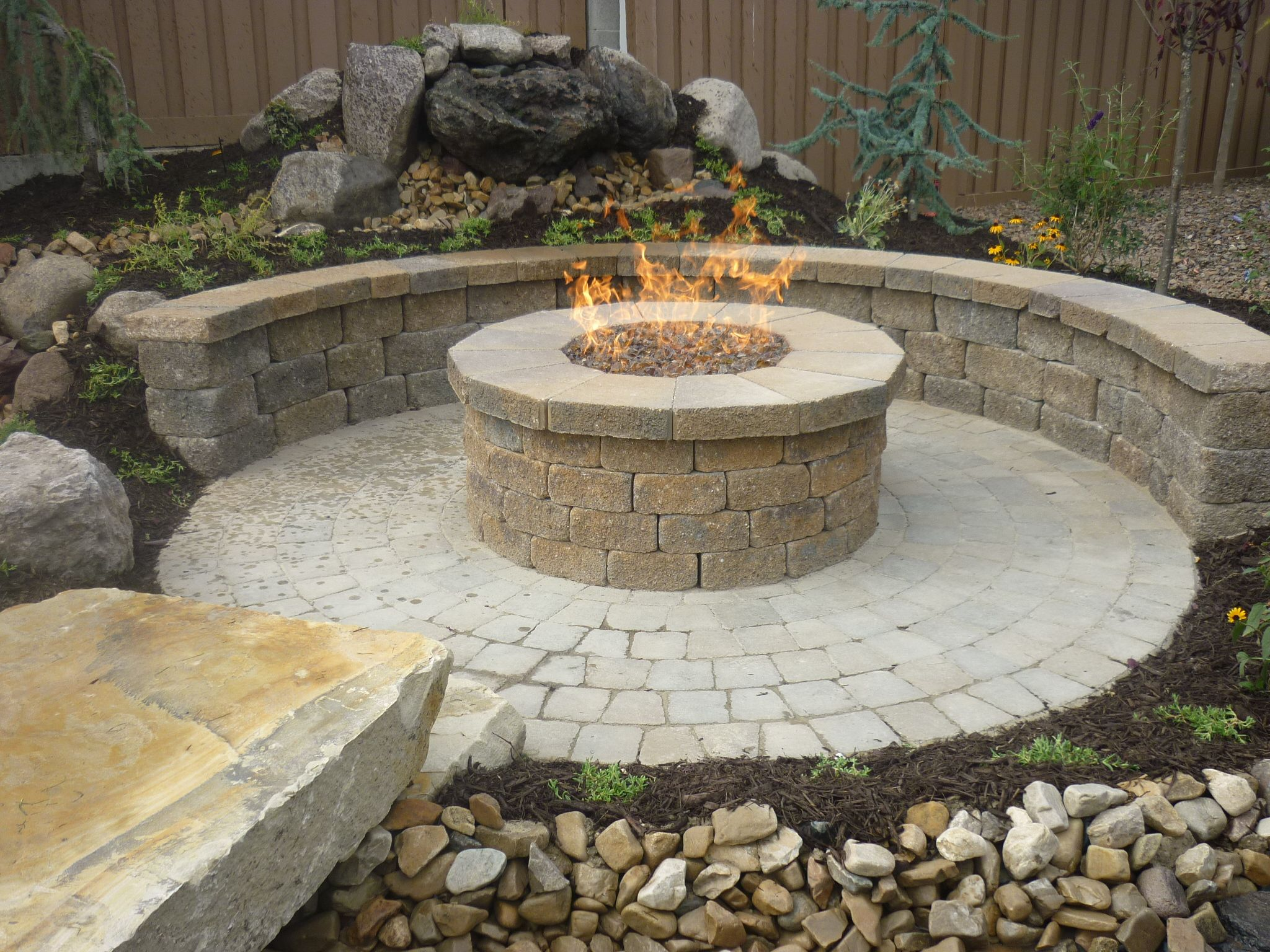 Stone fire pit designs patio traditional with artistic hardscape - Paver Patio Circle Paver Wall In Country Manor Paver Raised Natural Gas Fire Pit With Glass Rocks Water Feature Around It For The Perfect Natural