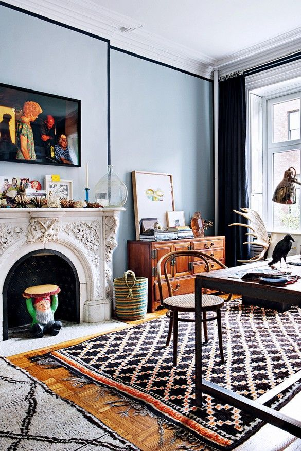 gray living room walls trimmed with black paint a classic carved marble fireplace and colorful moroccan area rug