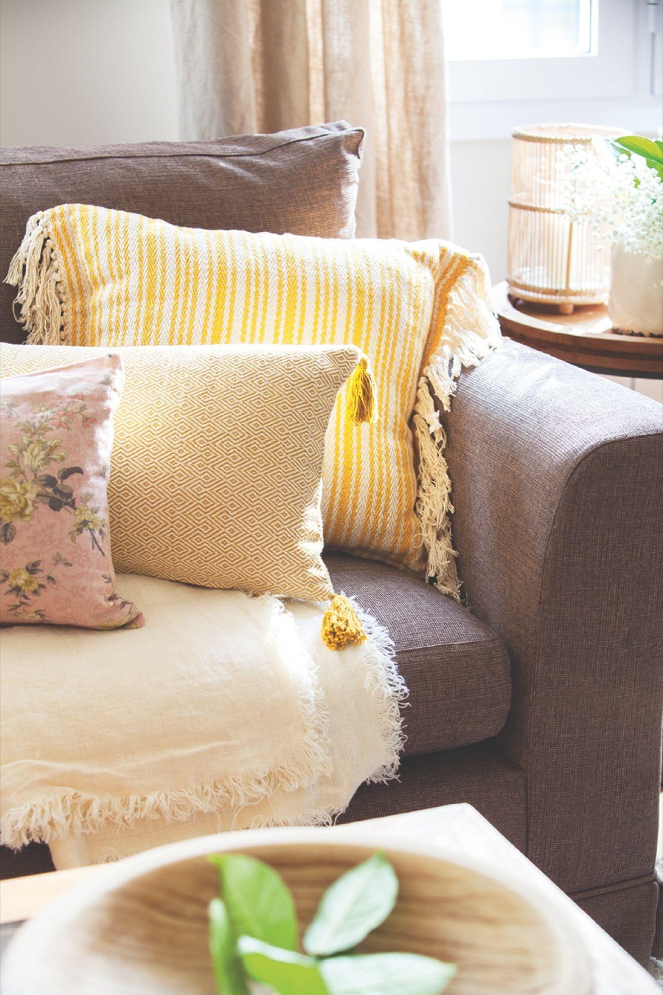 Salóncomedor con sofá gris cojines en rosa y amarillo mesa de