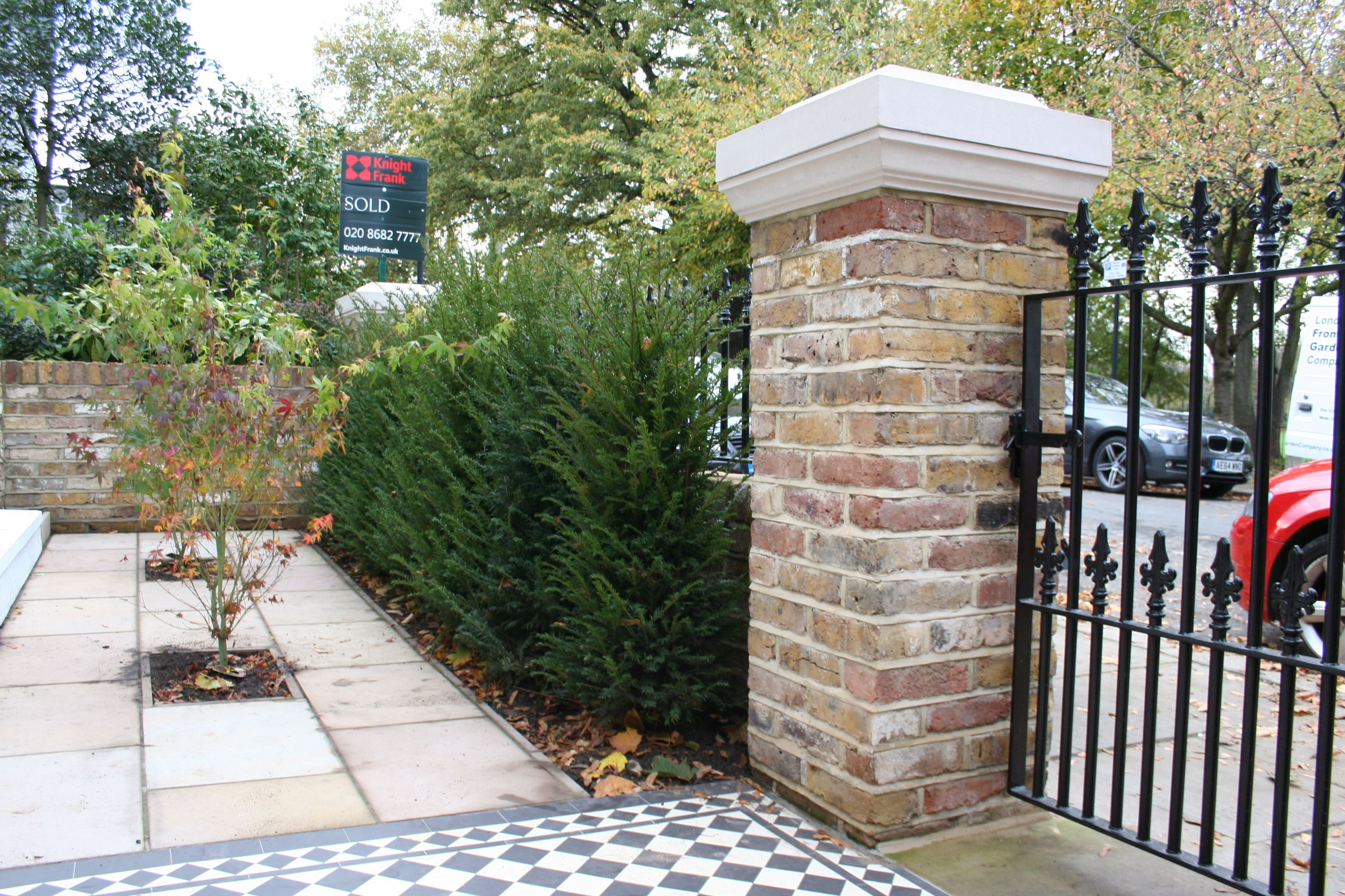 Brick pillar and black railings in contemporary london front garden