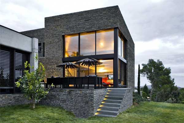 Modern home integrated in its surroundings mont r s for Modern stone houses architecture