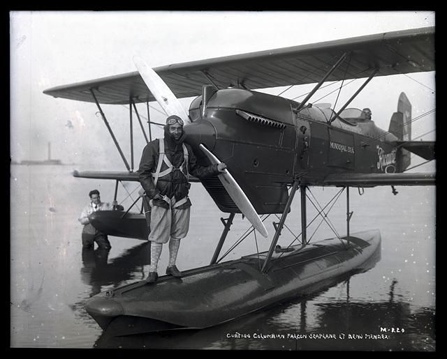 "November 18, 1928: Curtiss Falcon Model 37F Seaplane ""Ricaurte"" at rest in shallow water, pilot Lt. Benjamin Mendez stands on the aircraft's float. Source: National Air and Space Museum Archives"