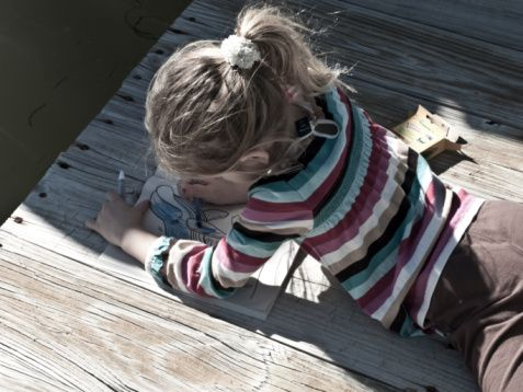 Muted colored image of a girl coloring on a dock.