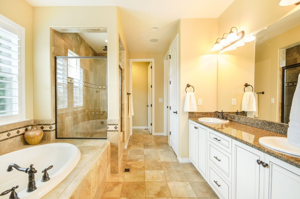 If your bathroom already has white cabinets and doors, you can add warmth  to the