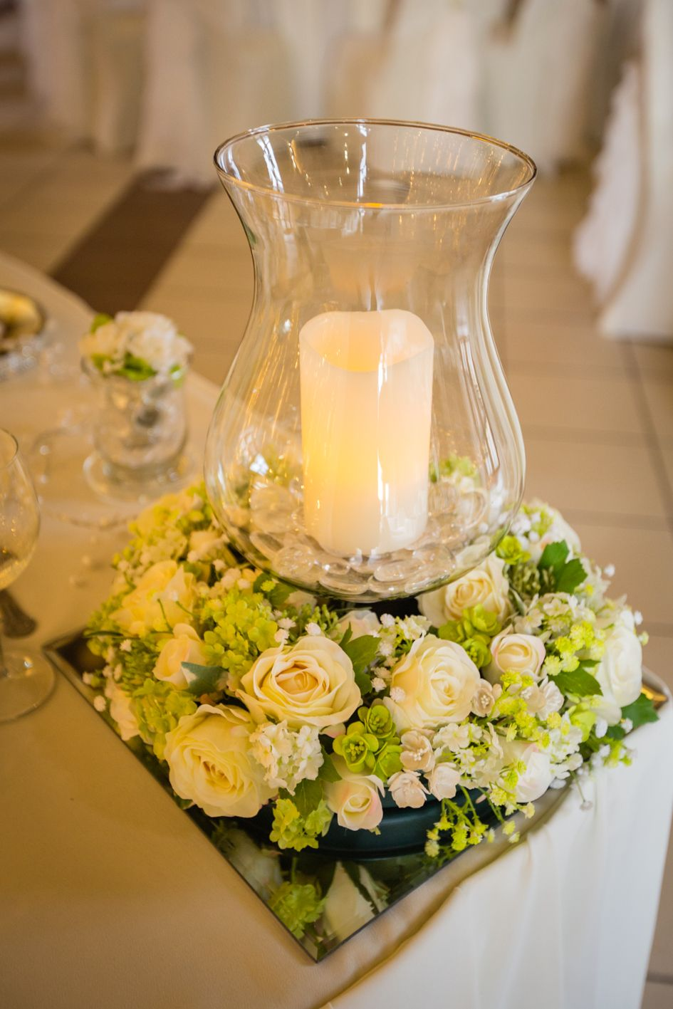 Beautiful arrangement marking either end of the top table hurricane vase with chunky candle atop a square mirror plate with copious luxury green and ivory ... & Beautiful ivory and green flowers surrounding a hurricane vase with ...