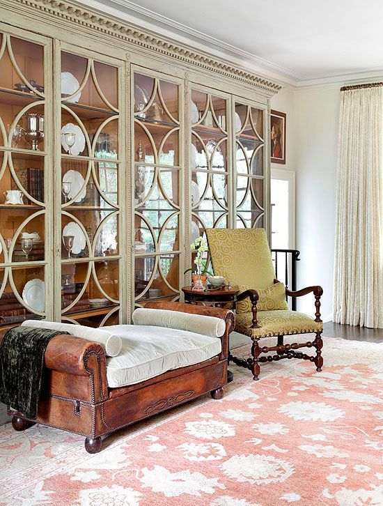 A large glass-front antique cabinet wears its original sage green ...