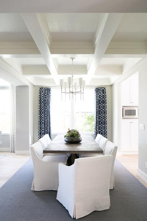 White Low-back Slipcovered Dining Chairs Surround A Dark