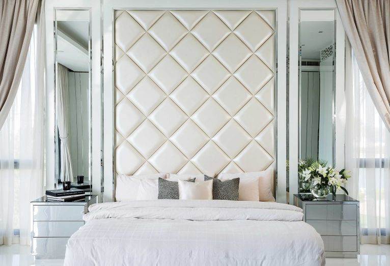 A Quilted Headboard And Mirrored Wall Panels Create A Hotel At Home Feel In The Master Bedroom Wall Panels Bedroom Modern Bedroom Decor Hotel Mirrors