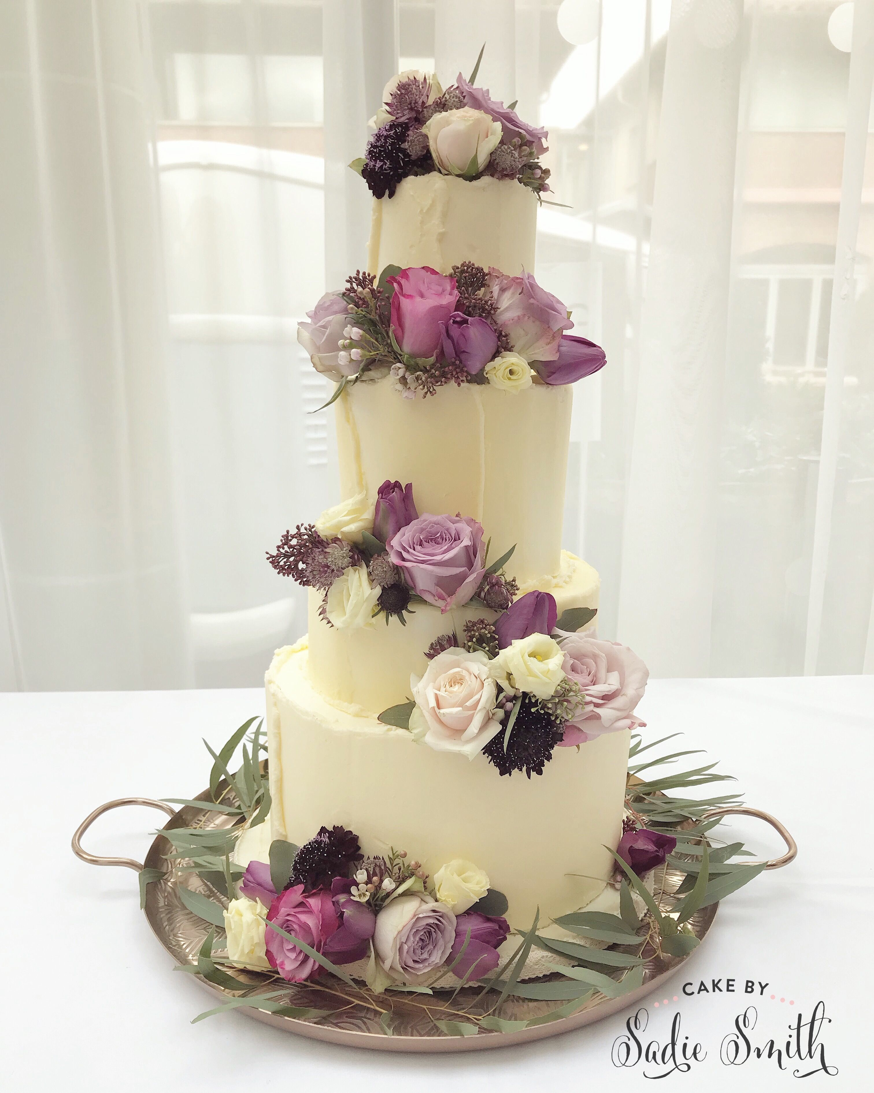 A rough edged textured wedding cake decorated with pastel