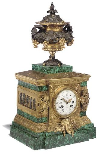 A NAPOLEON III ORMOLU, PATINATED BRONZE AND MALACHITE-VENEERED MANTEL CLOCK  BY DENIÈRE, PARIS, THIRD QUARTER 19TH CENTURY  Surmounted by a vine-garlanded urn, the case of rectangular architectural breakfront shape, the dial inscribed DENIERE/FT. DE BRONZES/A PARIS and flanked by further vine-leaf decoration, the stepped base headed by a Bacchus mask  20½ in. (52 cm.) high; 11 in. (28 cm.) wide