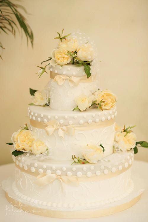 White wedding cake with soft yellow flowers and and ribbons. Lovely ...