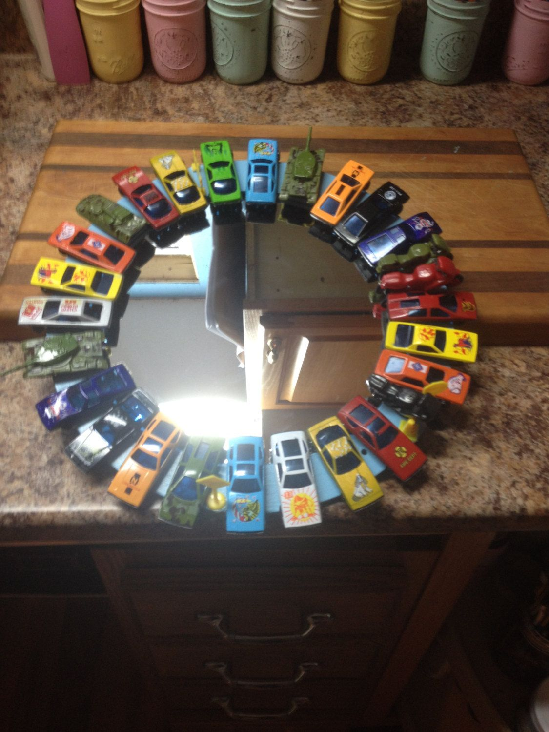 """Car Mirror for boys room by CreationsbyLaurieAnn on Etsy. Handmade with a 12"""" wooden wreath, match box cars, 9"""" mirror.  Great to decorate a little boys room with."""