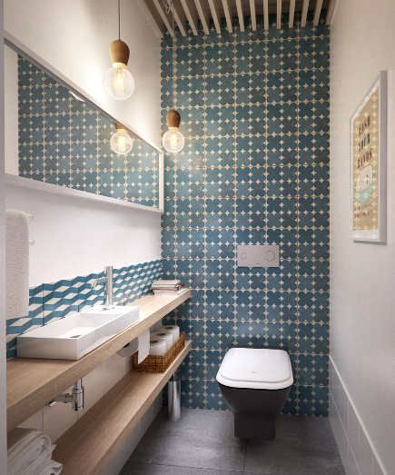 bathroom accent wall - blue and white geometric pattern tile on a commode  wall - architizer