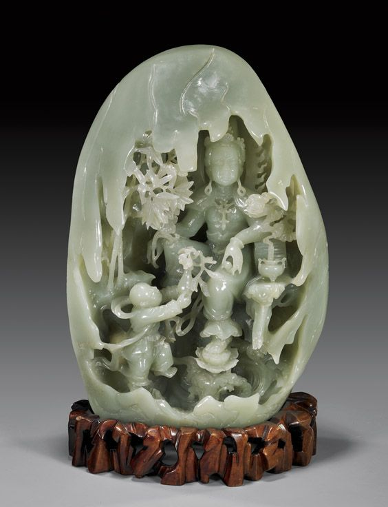 A celadon jade egg shaped boulder shelters an openwork