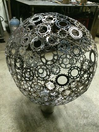 """This is a 28"""" in diameter ball made of bicycle sprockets welded together with more elements and light to  complete. It will free hang from a welded bracket"""