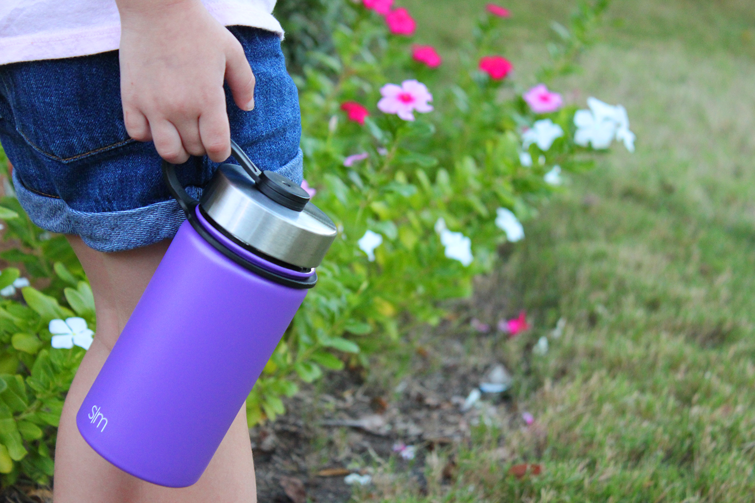 Little girl holding a Simple Modern 14oz Summit Bottle in lilac purple.