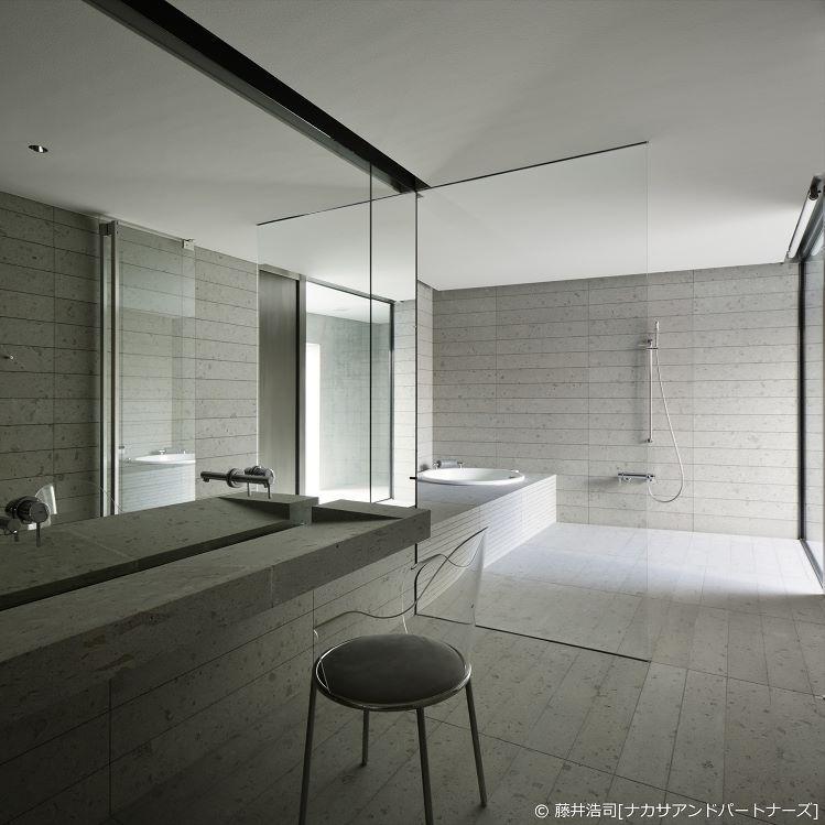 石材とガラスでシンプルにつくられたバスルーム On The Water 日建