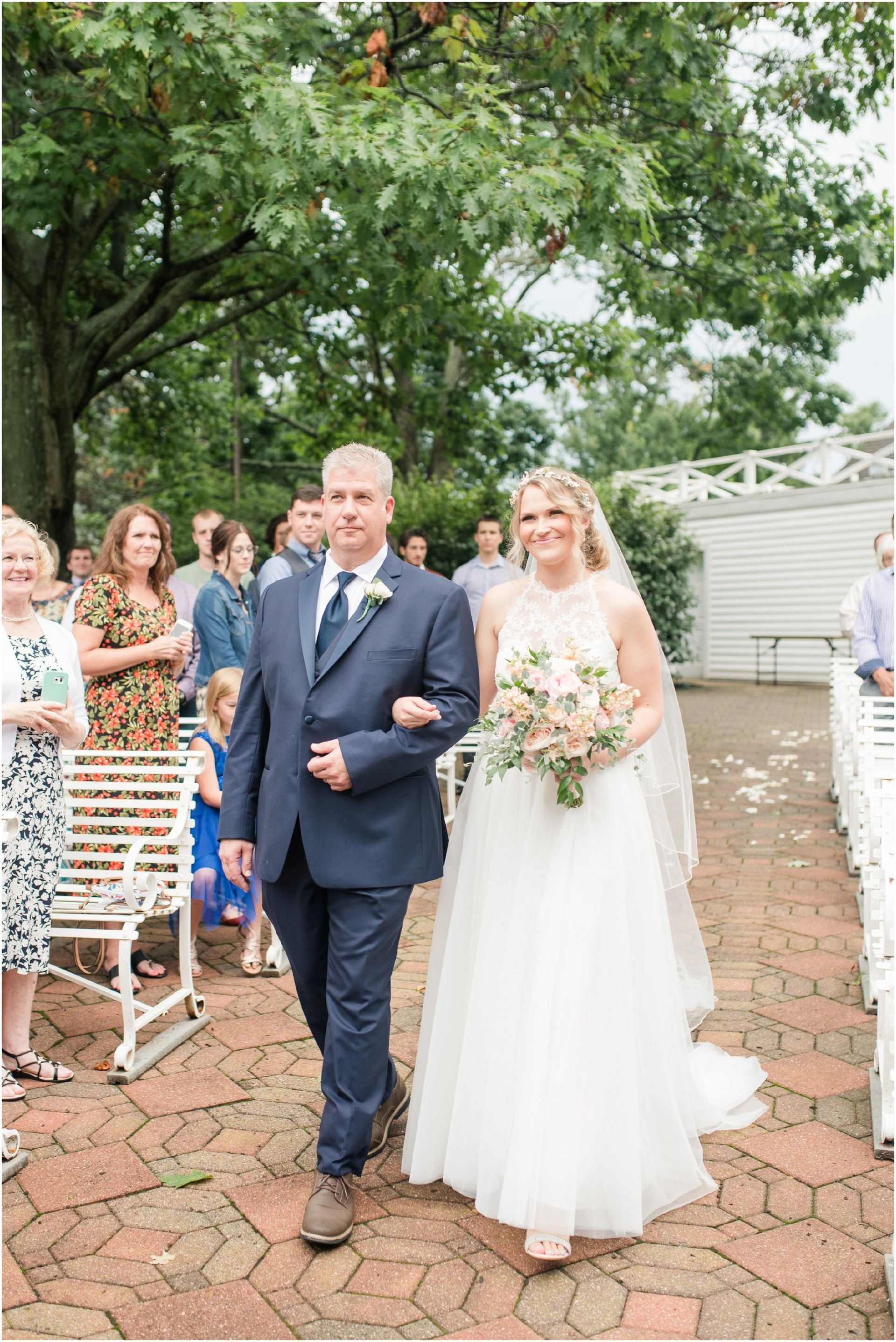 Bride Walking Down The Aisle On Her Wedding Day At An Outdoor Summer Ceremony The Flowerman Navy Suit Lace Two Piece Wedding Gown Brid Farm Wedding Wedding Bridal Formal