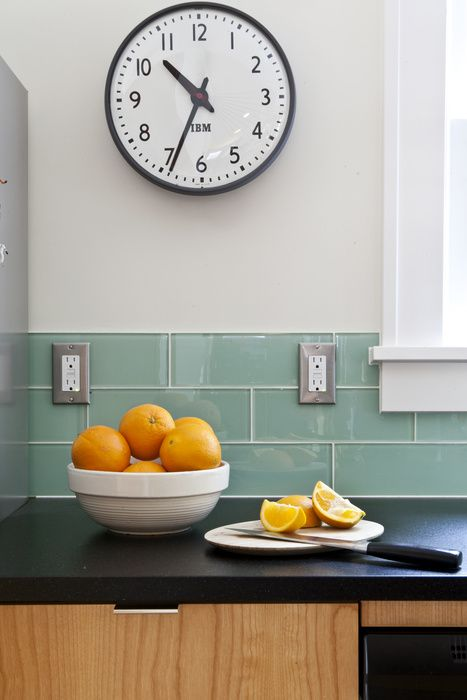 Well-balanced shot of oranges in a kitchen with black counter tops and wall clock. Photo by Vivian Johnson Photography.
