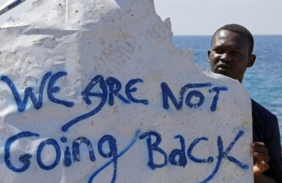 A migrant holds a banner at the Saint Ludovic border crossing on the Mediterranean Sea between Vintimille, Italy and Menton, France, June 15, 2015. REUTERS/Eric Gaillard
