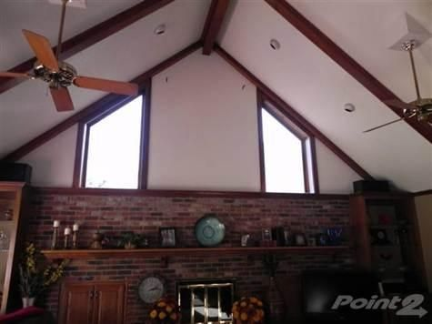 Living Room with vaulted ceiling. Solid oak bookcase. Brick fireplace with long mantle.