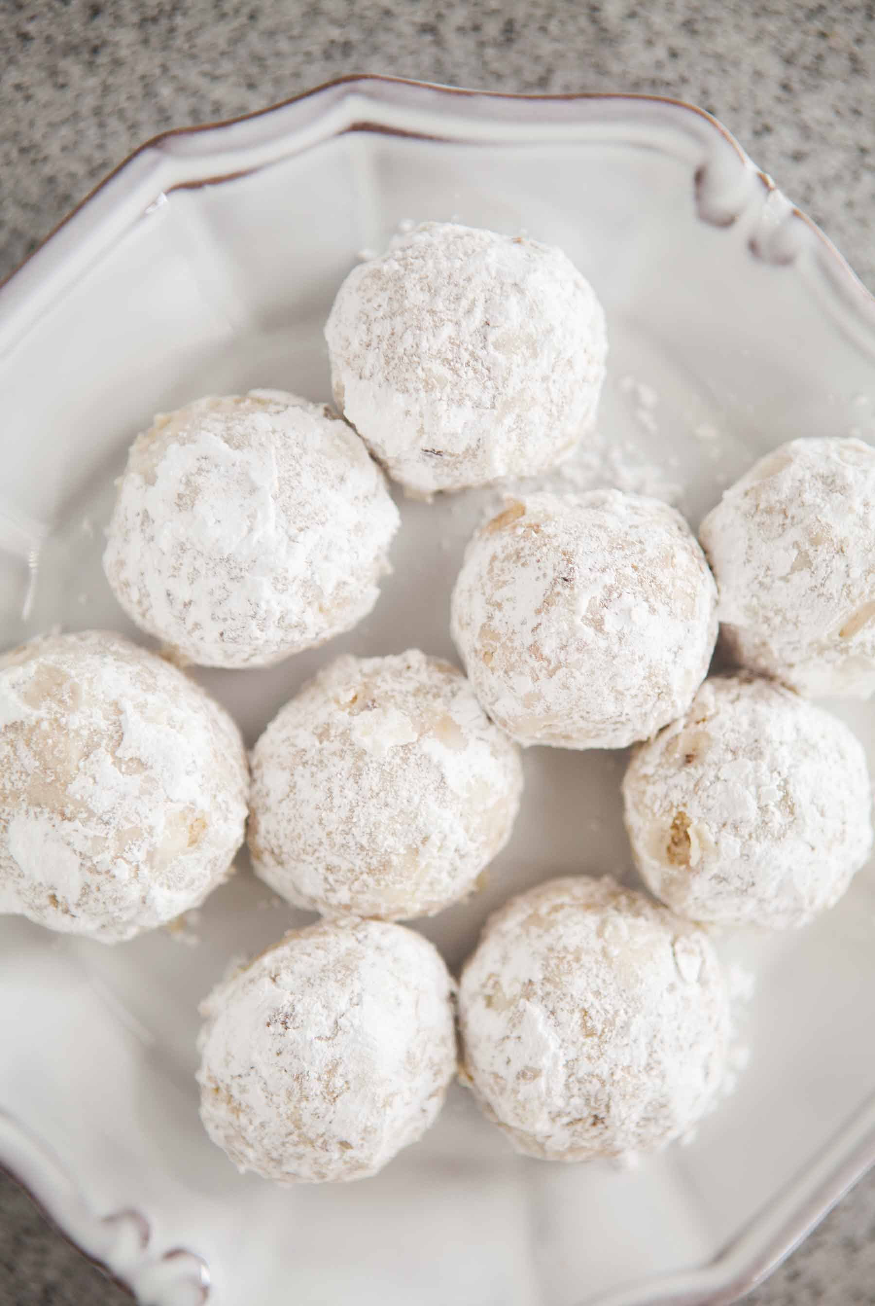 festive holiday snowball cookies made with finely chopped walnuts flour and vanilla rolled into balls and dusted with powdered sugar
