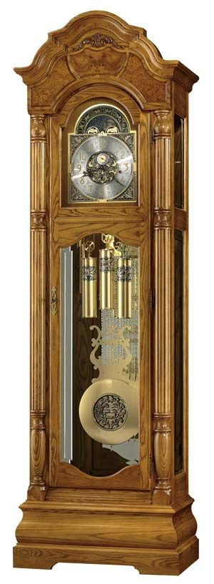 "Howard Miller Scarborough 611-144 Grandfather Clock. Special 82nd Anniversary Edition floor clock features a distinct bonnet pediment with book-matched olive ash burl overlays and a decorative carved applique. Brushed satin brass finished dial features cast center and corner ornaments, and a moon arch with an astrological blue moon phase. Finished in Legacy Oak. Key-wound, triple chime movement with automatic nighttime chime shut-off option. Size: H. 88-1/2"" W. 27"" D. 16"""