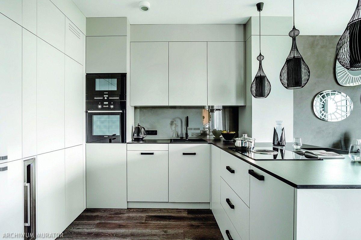 Zabudowa Bialej Kuchni Wykorzystuje Kazdy Centymetr Dzieki Czemu Zlewa Sie Praktycznie Z Otoczeniem Wysoka Kitchen Cabinets Modern Loft Organizing Your Home