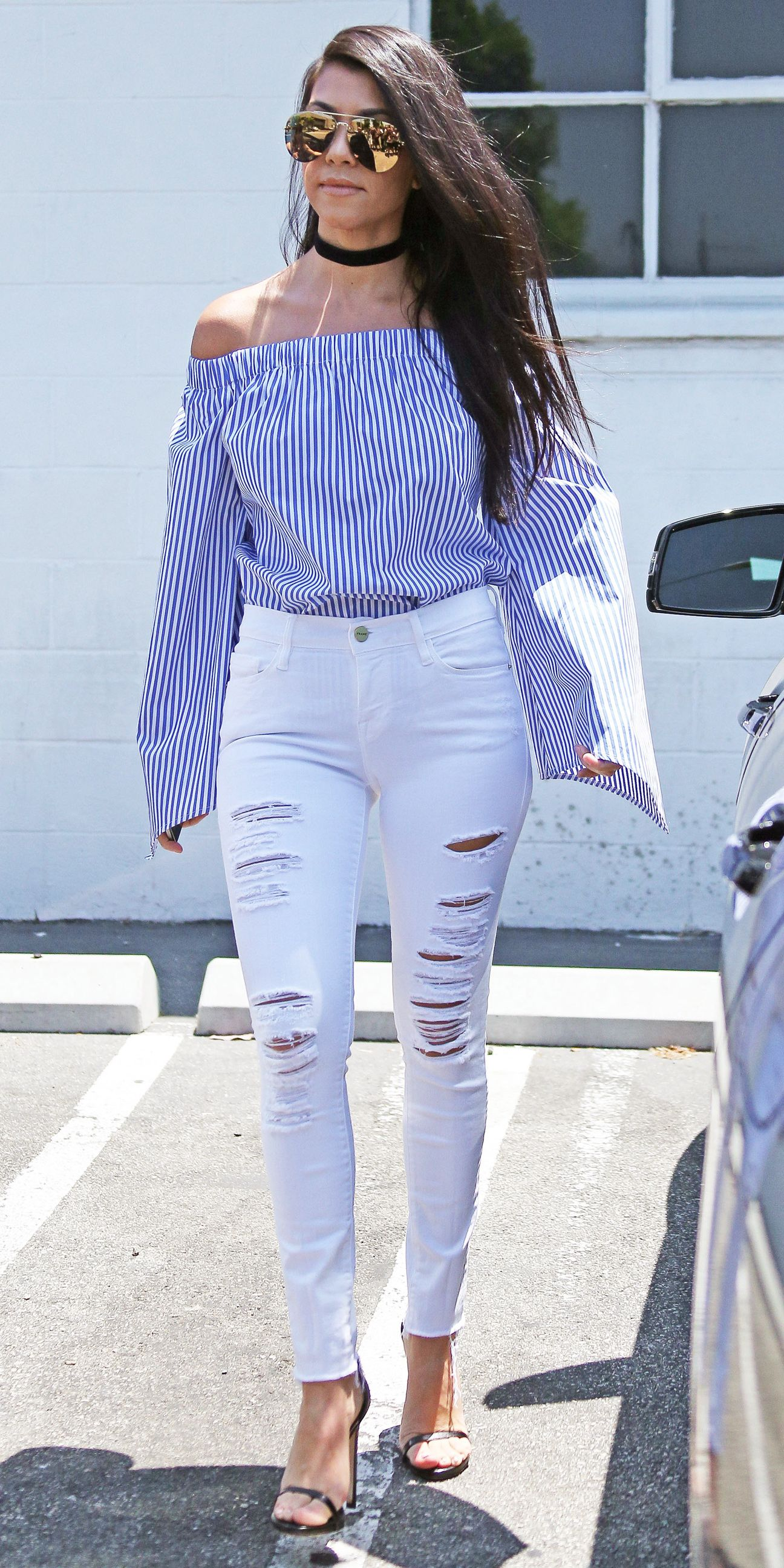 a960afa52bd Kourtney Kardashian in a blue-and-white striped off-shoulder top that she  styled with white destroyed jeans